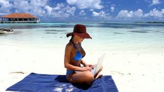 Beautiful woman working on laptop near water at Maldives