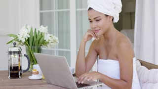 Beautiful woman wrapped in white towel working at table on her laptop computer beside flowers and coffee outside