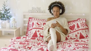 Beautiful young adult woman in long sweater and stocking resting on bed while listening to music on her mp3 player