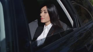 Beautiful young executive sitting in limousine