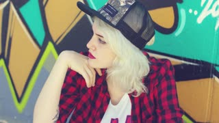 Beautiful young hipster blond woman wearing a baseball cap with a pierced lower lip sitting in front of colorful graffiti looking to the side with a serious expression.