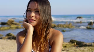 Beautiful young tanned brunette woman at the beach on a rocky coast looking at the camera with a beaming smile close up head and shoulders