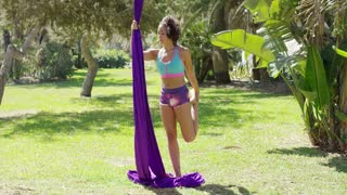 Beautiful young woman acrobatic dancer standing on the ground in a tropical park holding her silk ribbons and doing stretching exercises