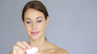 Beautiful young woman applying face cream to her cheek bone in a beauty skincare or cosmetics concept on grey with copy space