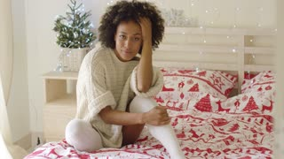 Beautiful young woman sitting in bed with Christmas theme decorations and tree behind her