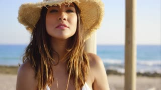 Beauty in white swim suit stares at camera wearing straw hat near ocean on pleasant summer day