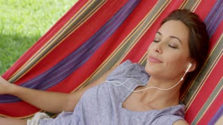 Blissful young woman relaxing listening to music in a colorful striped hammock outdoors in the garden looking at the camera with a happy smile