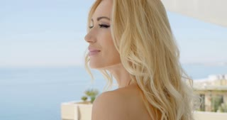 Blond Woman Admiring View from Ocean Front Balcony