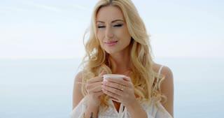 Blond Woman Drinking Coffee on Ocean Front Balcony
