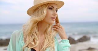 Blond woman enjoying the breeze on the seashore