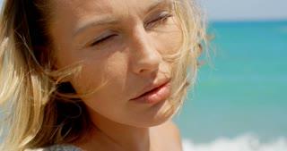 Blond Woman Enjoying Warm Sunshine on Beach