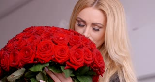 Blond Woman Holding a Bouquet of Fresh Red Roses