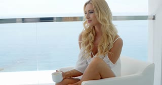 Blond Woman Holding Mug and Admiring VIew of Ocean