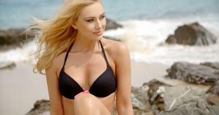 Blond Woman in Bikini Looking Down on Rocky Beach