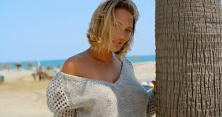 Blond Woman in Sheer Sweater Next to Tree at Beach