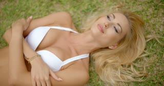 Blond Woman in White Bikini Lying on Grass