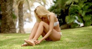 Blond Woman in White Bikini Sitting on Grass