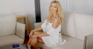 Blond Woman in White Dress Sitting on Sofa