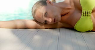Blond Woman Lying on Side Next to Swimming Pool