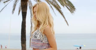 Blond Woman on Beach Smiling Over Shoulder