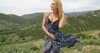 Blond Woman on Windy Hill near Wind Farm