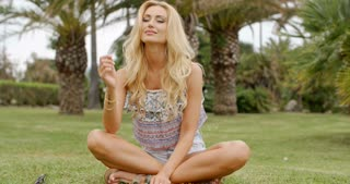 Blond Woman Sitting Cross Legged on Grass