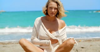 Blond Woman Sitting Crossed Legged on Beach