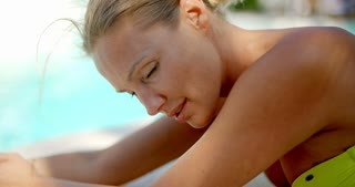 Blond Woman Smiling at Camera by Swimming Pool