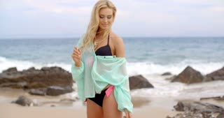 Blond Woman Standing on Beach with Open Arms