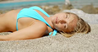 Blond Woman Suntanning on Beach with Eyes Closed