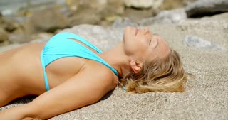 Blond Woman Wearing Bikini Lying on Sandy Beach