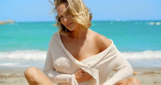 Blond Woman Wearing Cover Up Sitting on Beach