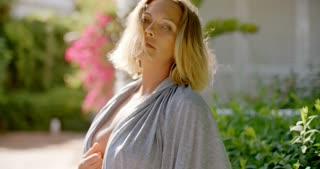 Blond Woman Wearing Open Grey Robe in Garden