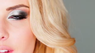 Blue eye and makeup of a beautiful blond woman wearing creative modern cosmetics closeup view of half the face