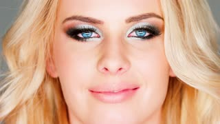 Blue eye and makeup of a beautiful smiling woman looking into the camera closeup view