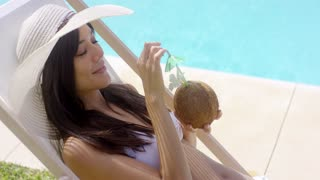 Brown haired woman in white bikini with sun hat on a beautiful summer day holding a coconut drink