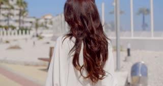 Brunette Woman in Sunglasses on Beachfront Walk