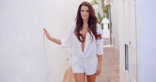 Brunette Woman Standing Outdoors with Hand in Hair