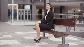 Calm business woman sitting outdoors