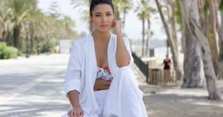 Calm woman in white robe sitting outdoors