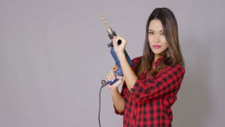 Capable attractive young woman holding an electric drill in her hands in a DIY or renovations concept over grey