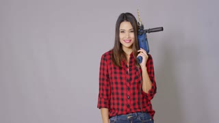 Capable young woman holding a power drill in her hand giving a thumbs up gesture of approval and success with a happy smile over a grey background with copy space.