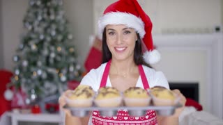 Charming young woman wearing a festive red Santa hat with fresh baked Christmas cookies in an oven tray offering them to the camera with a smile.