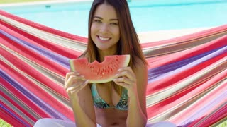 Cheerful young woman eating one watermelon slice while sitting on hammock stretched out behind her