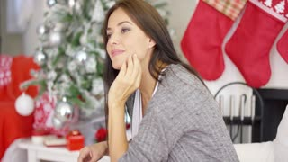 Cheerful young woman sitting with her chin resting on her hand and a pensive expression as she celebrates the holiday season in a Christmas decorated home close up profile view.