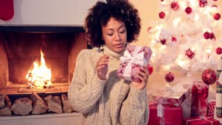 Close up of beautiful black woman holding present while seated by fireplace
