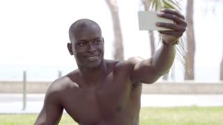 Close up of shirtless black man with phone