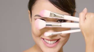 Close up on beautiful woman holding three different sized makeup brushes in front of face