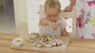 Close up on cute girl sprinkling toppings on various flavored little muffins on wooden table with copy space
