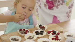 Close up on cute little girl with serious expression putting berries on muffins in paper cups on table